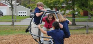 An image of 4 children playing on playground equipment.