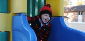 An image of a smiling little boy on playground equipment.